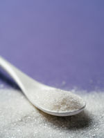 Sugar in white spoon on violet, copy space