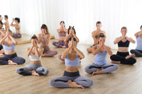 Group of young sporty attractive people in yoga studio, practicing yoga lesson with instructor, sitting on floor in Sukhasana meditative yoga pose. Healthy active lifestyle, working out in gym