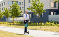 businessman with shopping bag riding scooter