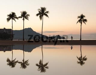 Sunrise over ocean with palm trees in Waikiki Hawaii