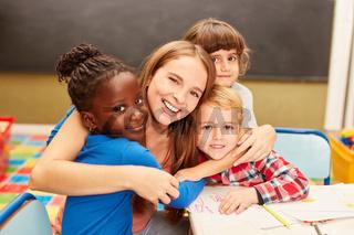 Erzieherin umarmt Kinder in der Kita