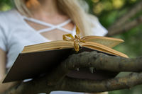 Old book lying on the tree branch in front of reading girl