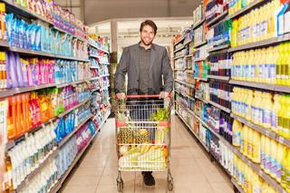 Lächelnder Mann schiebt einen Einkaufswagen