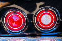 Red round rear lights of a black sport car
