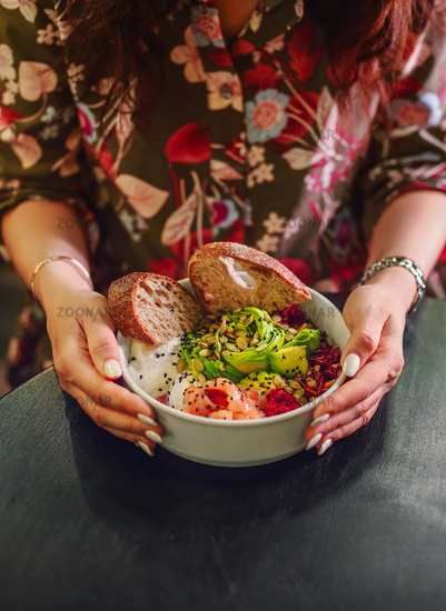 Woman eating organic food. Fresh seafood recipe. Fresh salmon poke bowl with rice, egg, bread, fresh red cabbage, avocado, radish sprouts on dark background