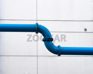 A water pipeline across the city in front of a plain facade
