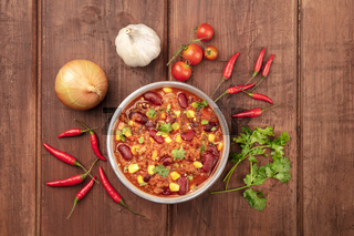 Chili con carne, shot from the top on a dark rustic wooden background with ingredients