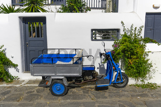 Motor tricycle with basket parked against whitewashed house.
