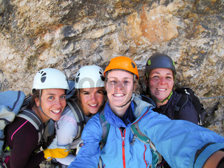 four female climbers celebrate on the mountain summit by taking a group photo