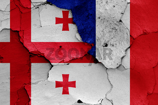 flags of Georgia and France painted on cracked wall