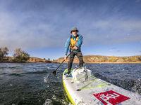 senior man paddling a stand up paddleboard