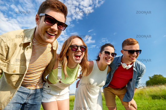 happy teenage friends laughing outdoors in summer