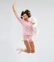 happy woman in pajama jumping with pillow