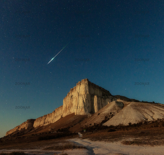 Night star sky and meteor over rock