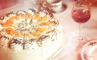 Part of a coffee table with tangerine-cream-cake, rose wine glass and tableware