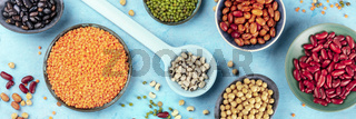 Legumes, overhead panoramic shot on a blue background. Vibrant pulses including colorful beans, lentils, chickpeas, a flat lay composition