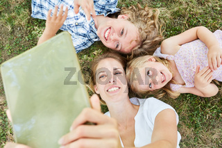 Mutter und zwei Kinder mit Tablet Computer