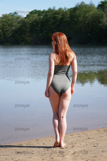 rear view of young woman wearing khaki one-piece swimsuit standing on beach at bathing lake