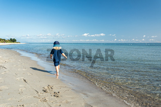 Young child walking down the beach at the beautiful blue ocean