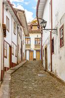 Facade of old houses built in colonial architecture and cobblestone street