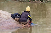 Unrecognizable woman doing the laundry in a river