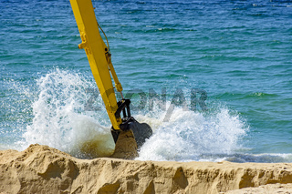 Backhoe removing sand from the beach and playing in the sea with water spray