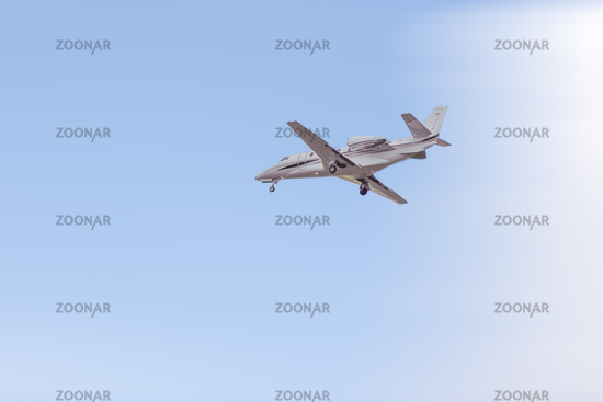 Private jet flying in the blue sky