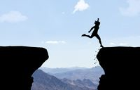 Woman landing after jumping over abyss in front of mountain background.