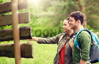 smiling couple at signpost with backpacks hiking
