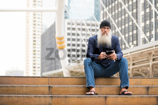 Mature bearded businessman sitting while using phone in the city outdoors