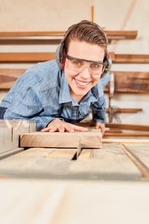 Schreiner Lehrling sägt Holz an der Kreissäge