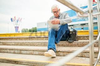 Elderly businessman using tablet on steps