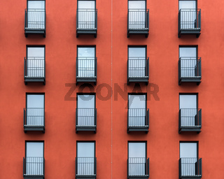 Front of a new red residential house with black balconies