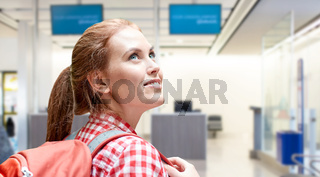 young woman with backpack over airport terminal