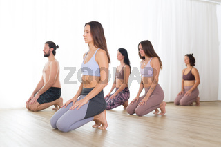 Group of young sporty attractive women in yoga studio, practicing yoga lesson with instructor, kneeling down, stretching and relaxing after workout . Healthy active lifestyle, working out in gym