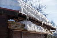 72/5000 Snow load on roof of a wooden house in the garden - close-up of garden hut