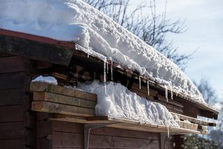 Schneelast auf Dach eines Holzhauses im Garten - Nahaufnahme Gartenlaube