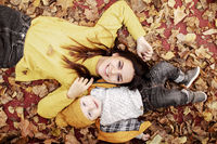 Young mother and baby lie on yellow leaves