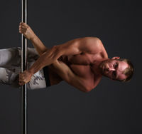 Studio image of male dancer exercising on pole