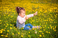 Young girl sitting on meadow, reaching out hand, blurred background
