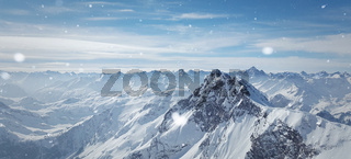 Snowy winter scenery with high moutains and snowflakes