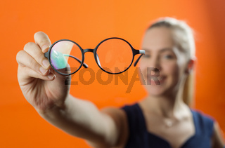 Woman showing glasses close to the camera. Blurred woman in background.