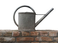 Old zinc watering can on a brick wall isolated.jpg