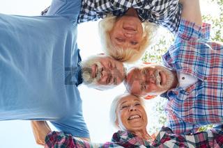 Glückliche Senioren stehen im Kreis