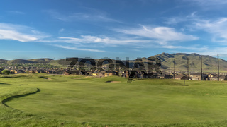 Panorama Golf course and houses with view of mountain towering in the distance