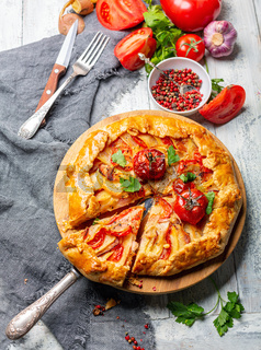 Open pie with potatoes, bacon and tomatoes.