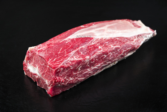 Raw dry aged wagyu beef top blade roast as closeup on black background with copy space