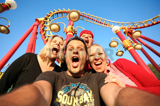 Multi ethnic friends on a rollercoaster ride at the fun fair