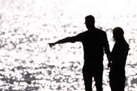 Blurred silhouette and shadow of a couple standing at the water