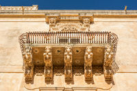 Beautiful ancient baroque balcony with horse ornaments in Noto